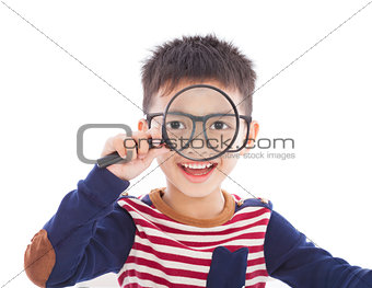 adorable boy holding a magnifier and watching through