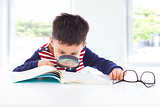 little boy detective searching clues from books