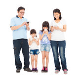 Family standing a row and using smart phone together