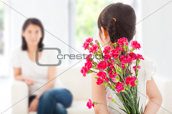 little girl looking at mother and hiding a bouquet of carnations