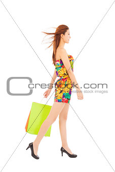 smiling asian woman walking and holding shopping bags