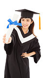 young woman college graduate wearing cap and gown holding diplom