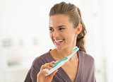 Happy young woman brushing teeth in bathroom