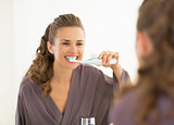 Young woman brushing teeth in bathroom