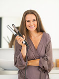 Portrait of happy young woman with hair straightener in bathroom