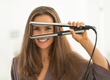 Happy young woman looking through hair straightener