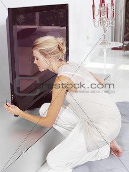 Beautiful blond woman sitting near tv