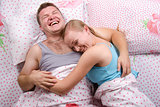 Young couple lying in bed and laughs