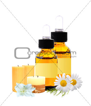 bottles with essence oil, candles and chamomiles