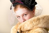 Redhead in black veiled hat and fur coat with mouth hidden