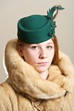 Redhead in green hat and fur coat