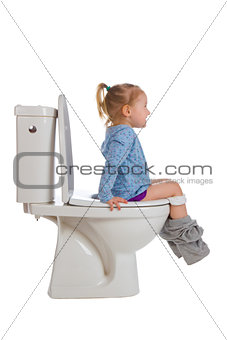 little girl is sitting on toilet