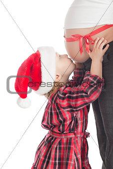 little girl kissing christmas gift - pregnant mother