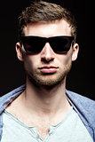 Portrait of handsome young man wearing sunglasses. Closeup