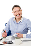 young smiling businesswoman looking at camera on her desk