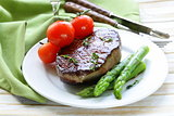 grilled meat beef steak with vegetable garnish (asparagus and tomatoes)