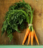 fresh organic carrots with green leaves on a wooden background