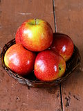Red ripe apples in a wicker basket on a wooden table