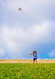 Sweet little girl running with kite