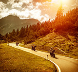 Bikers on mountains road in sunset