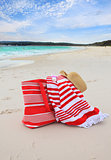 Beach bag towel and hat on the sand