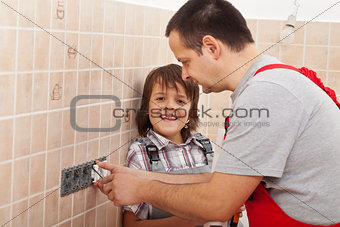 Boy assisting his father installing electical outlets