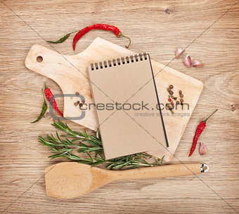 Blank notepad on cutting board with spices around
