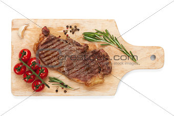 Sirloin steak with rosemary and cherry tomatoes on a cutting boa