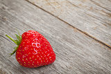 Ripe strawberry over wooden table background
