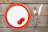 Plate with ripe strawberry and silverware