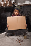 Poor beggar boy on the street with a cardboard sign