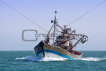 A fishing boat is at sea fishing.