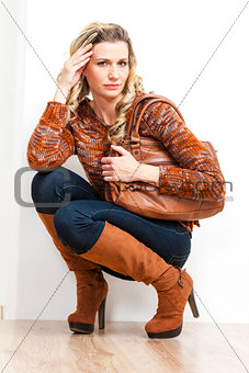 sitting woman wearing fashionable brown boots holding a handbag