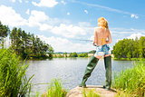 young woman fishing at pond in summer