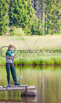 young woman fishing on pier at pond