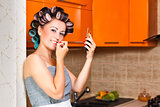 female middle-aged housewife paints her lips in the kitchen
