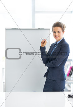 Portrait of smiling business woman near flipchart