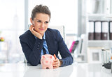 Thoughtful business woman with piggy bank