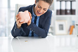 Angry business woman shaking out coin from piggy bank