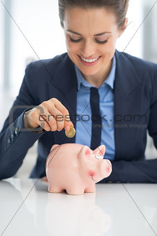 Business woman putting coin into piggy bank