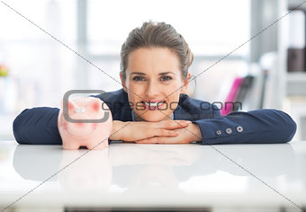 Portrait of happy business woman with piggy bank