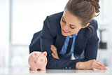 Happy business woman looking on piggy bank