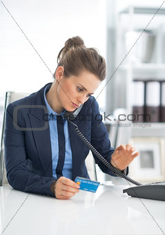 Business woman with credit card dialing phone