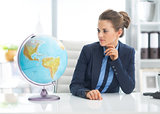 Business woman looking on earth globe