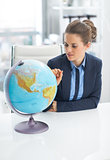 Business woman pointing on earth globe