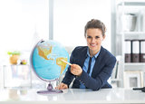Smiling business woman pointing on earth globe