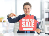 Happy realtor woman pointing on home for sale sign