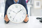 Closeup on business woman holding clock
