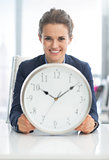 Smiling business woman holding clock