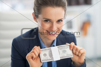 Portrait of happy business woman showing money pack